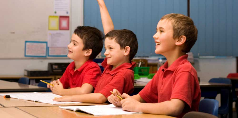 Three young boys smiling in class